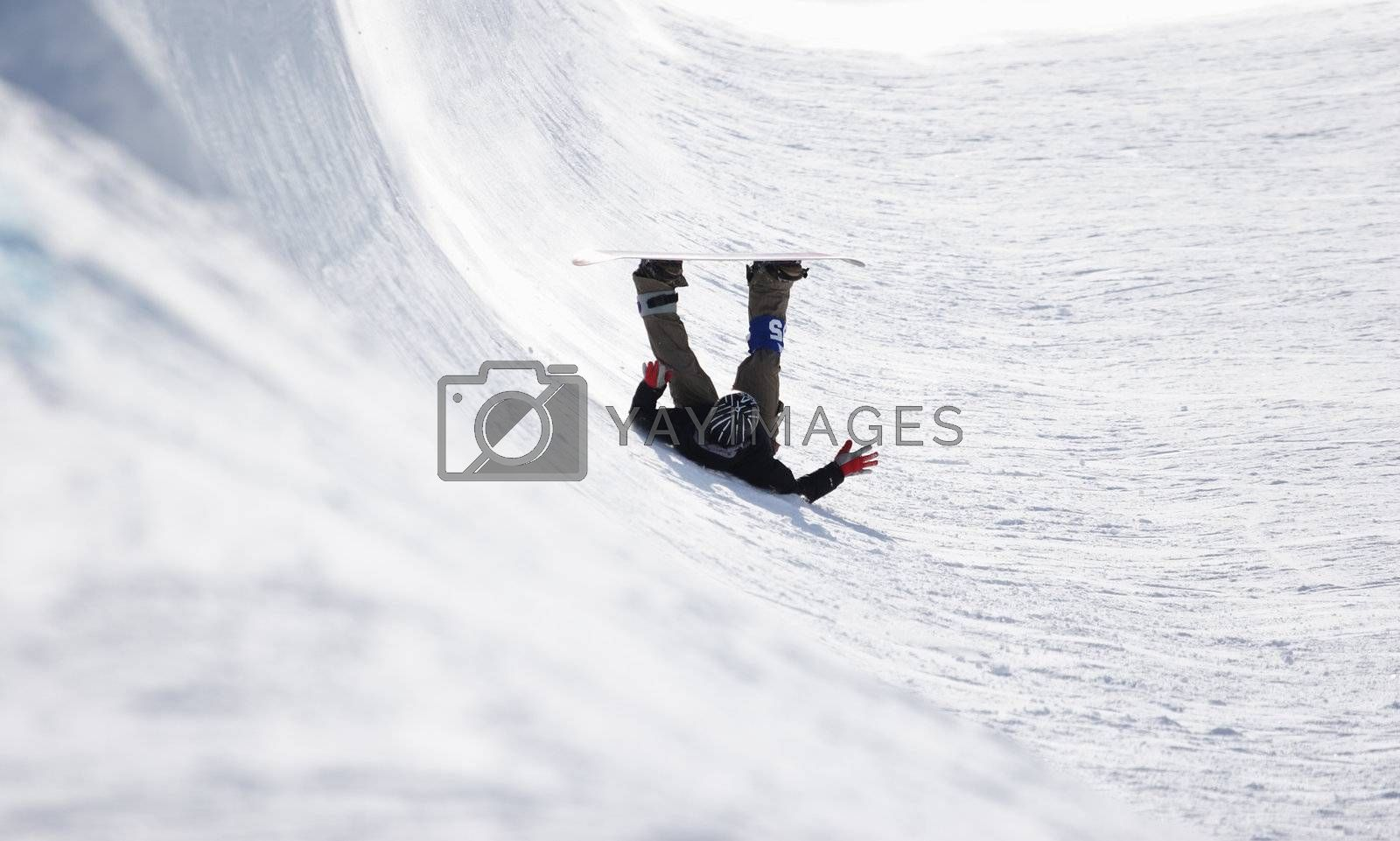 A snowboarder falls onto his back in a half pipe