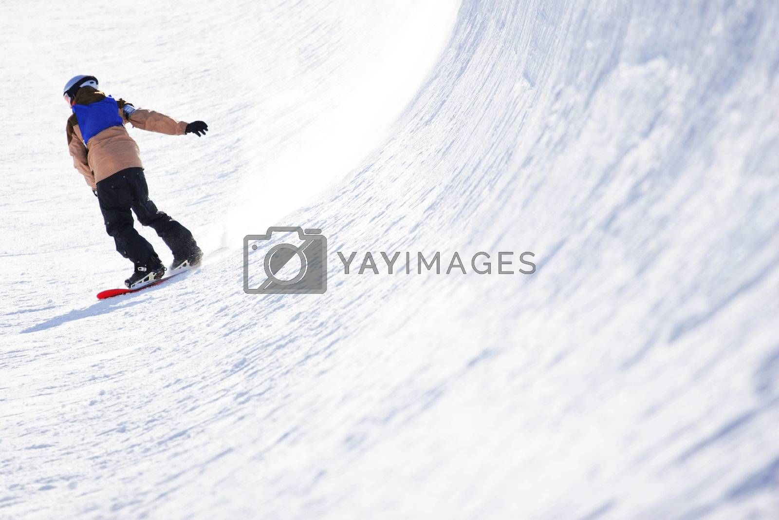 A snowboarder finishes a run in the half pipe
