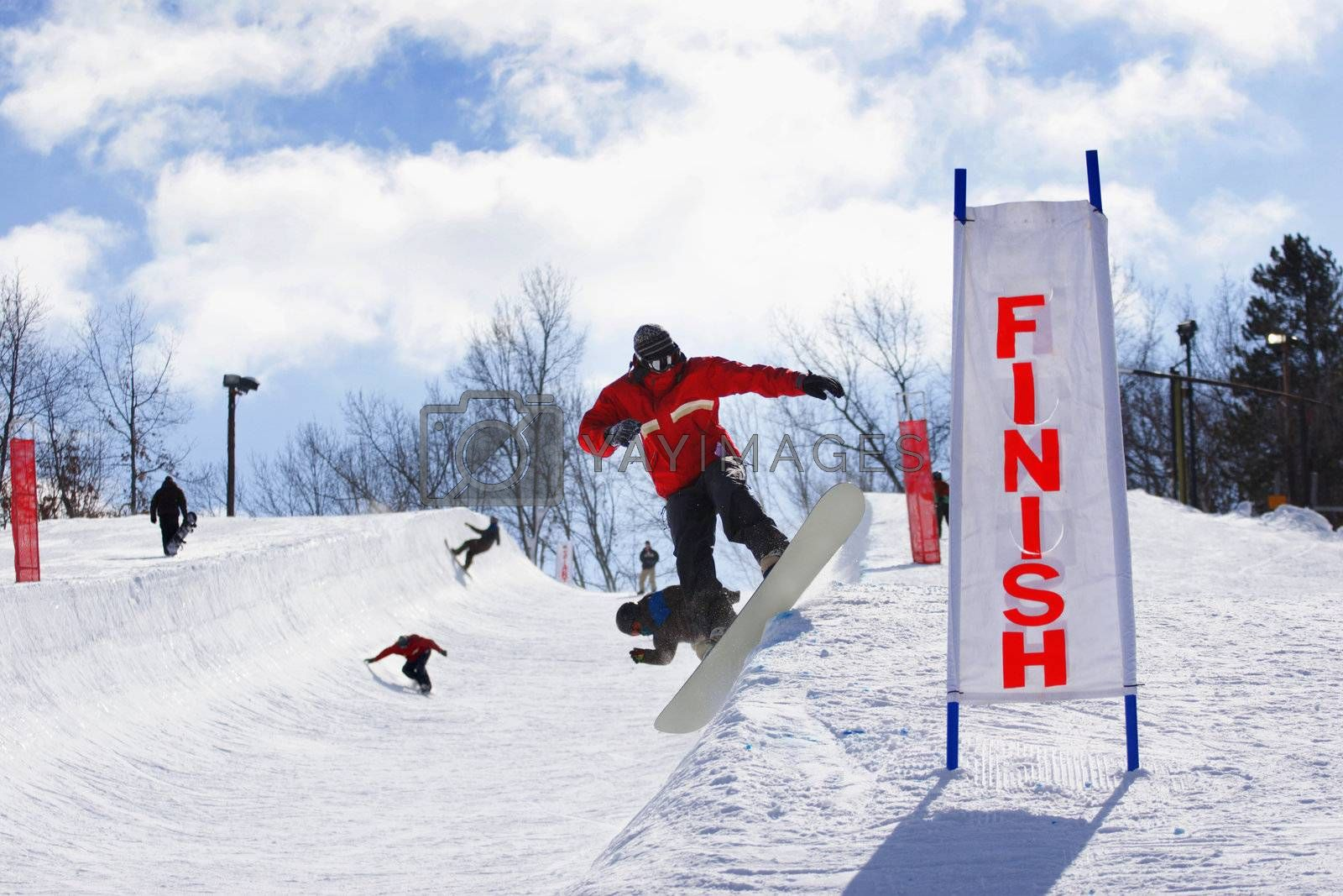 A group of snowboarders are warming up for a half pipe competition