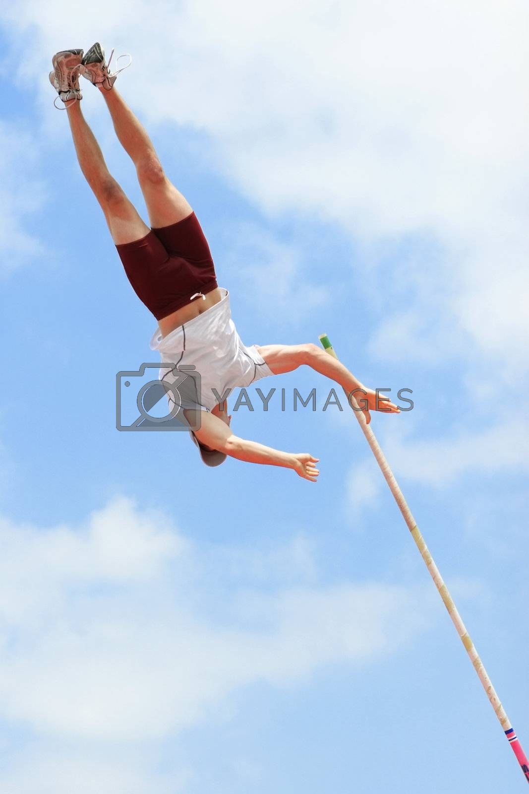 Pole vaulter has just released the pole while at the apex of his jump.