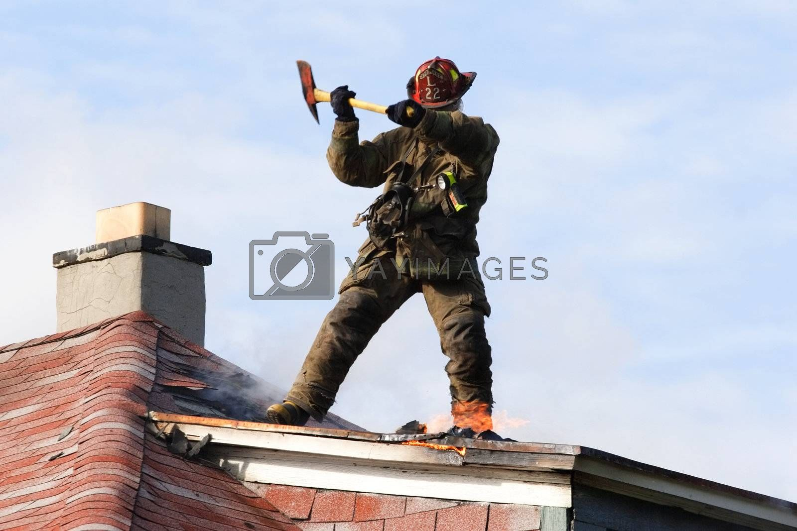 Firefighter standing on the roof of a house chopping at fire with an ax