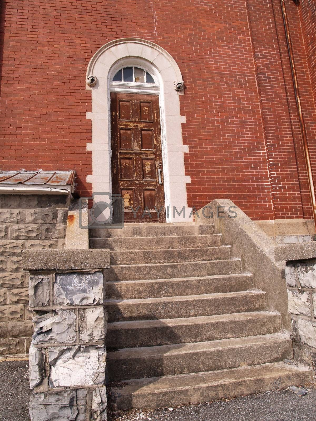 old wood door and steps for a red brick building