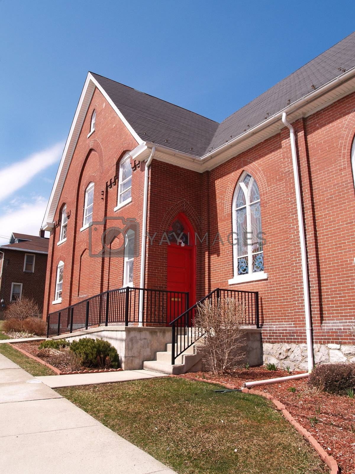 exterior of a red brick church with blue sky in the background
