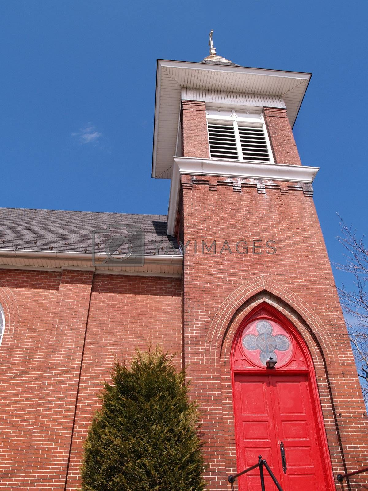 exterior of a red brick church with a red wood door and a blue sky in the background