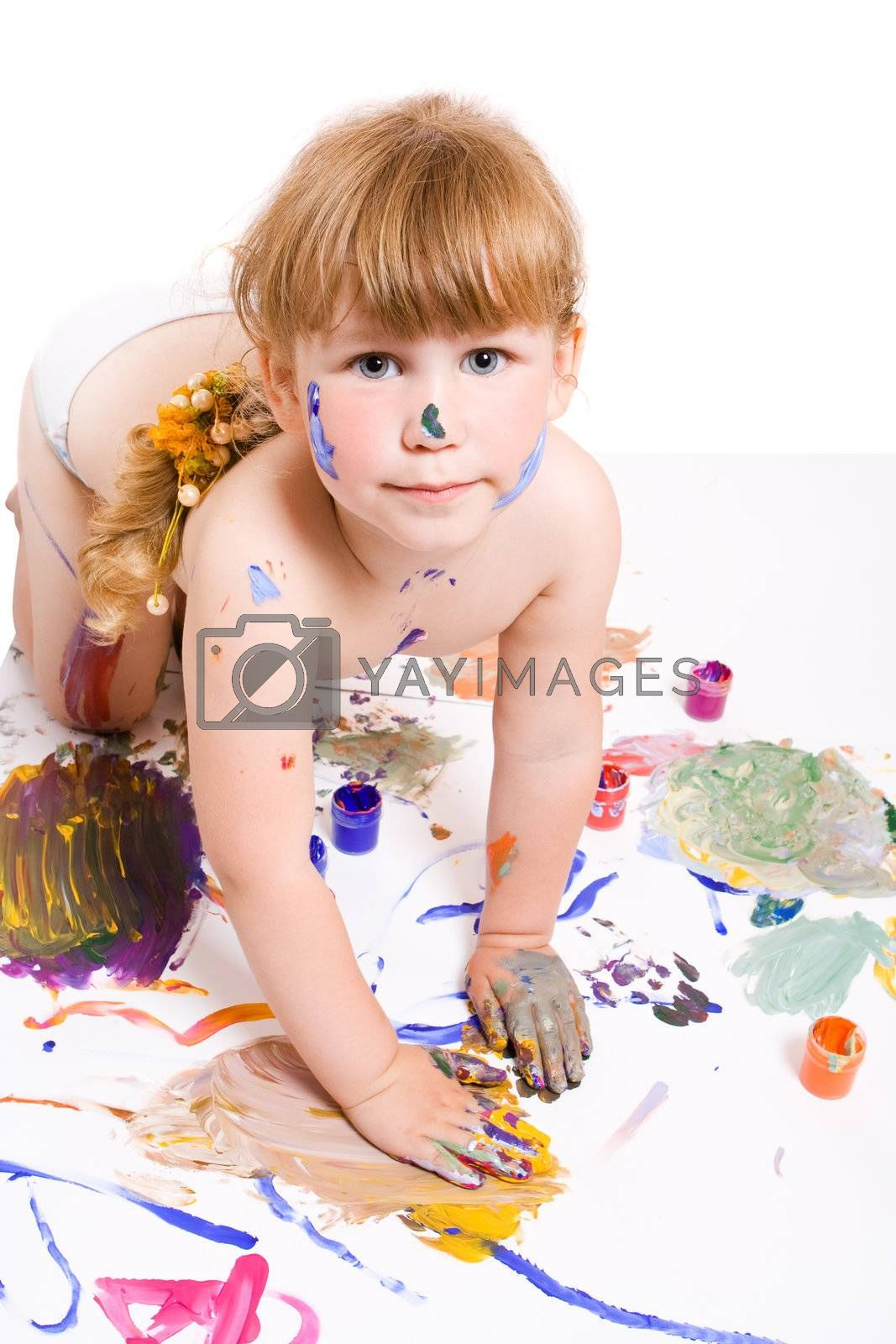 a girl with dirty face and hands of color paint seat on the dirty floor