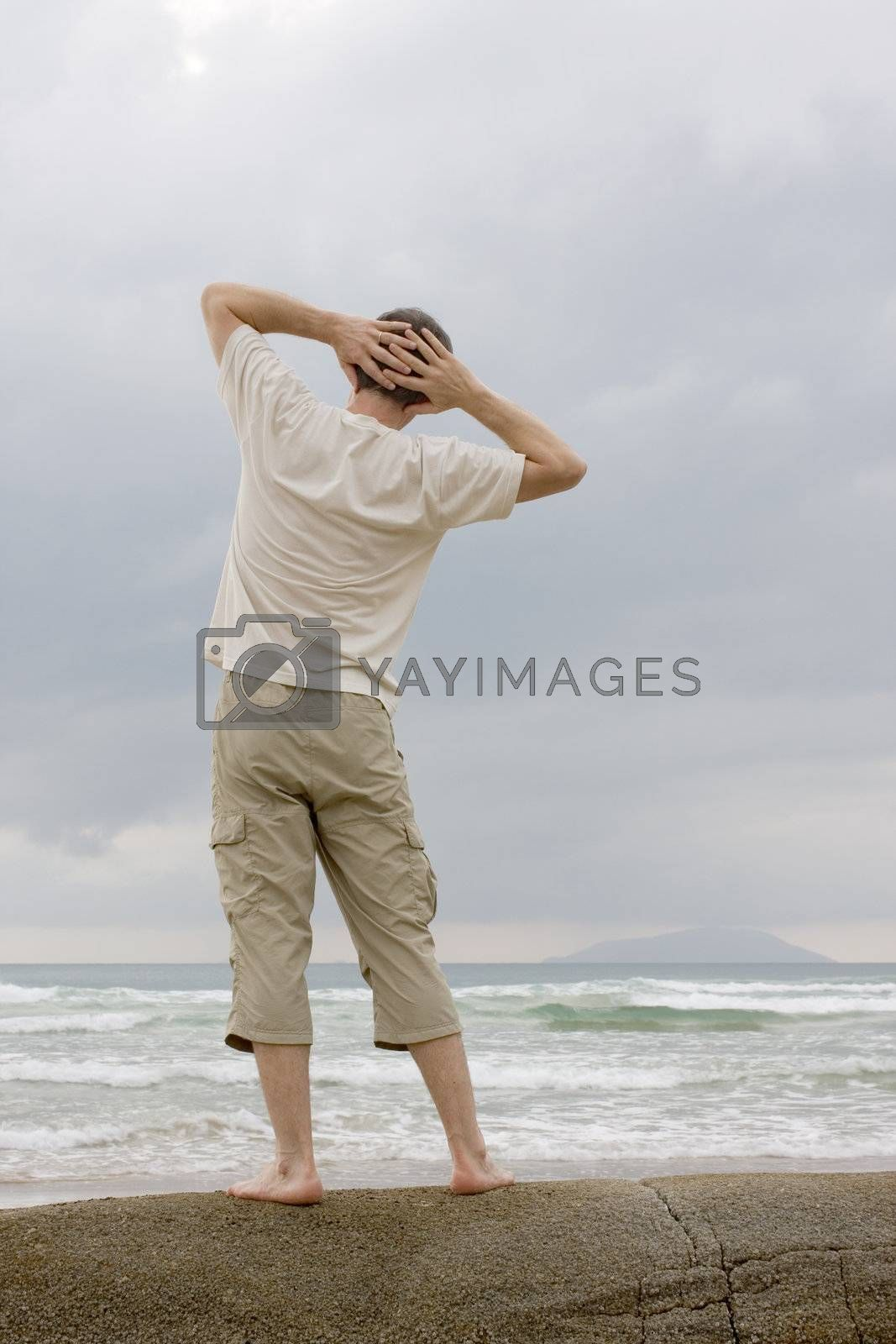 Man doing relaxing exercises on a rock at the sea
