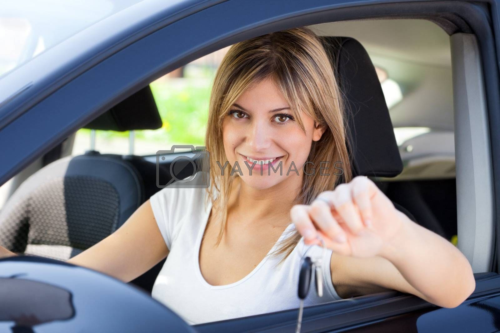 young man sitting inside car showing keys to new car