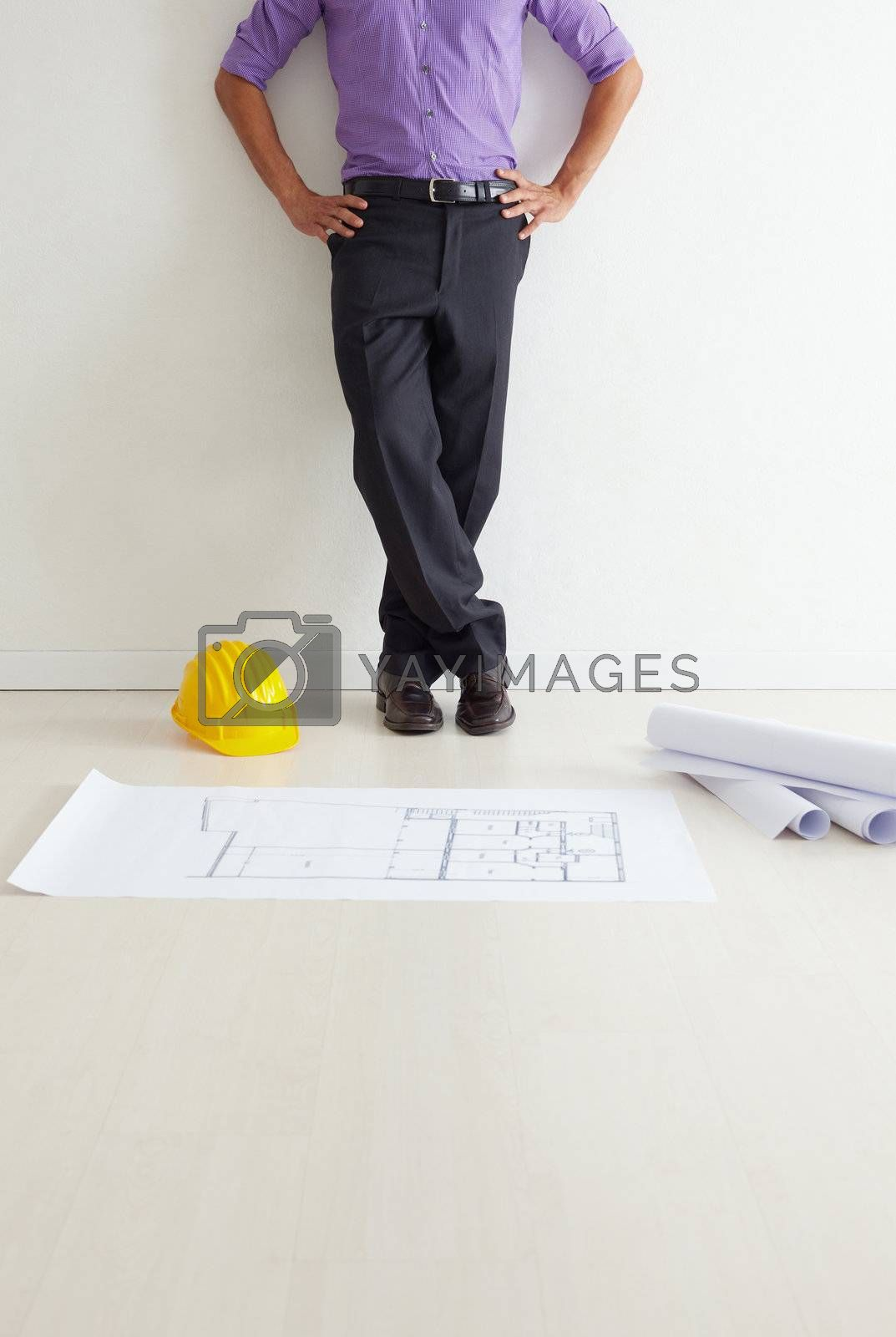 cropped view of mid adult architect leaning on wall and blueprints on floor. Copy space