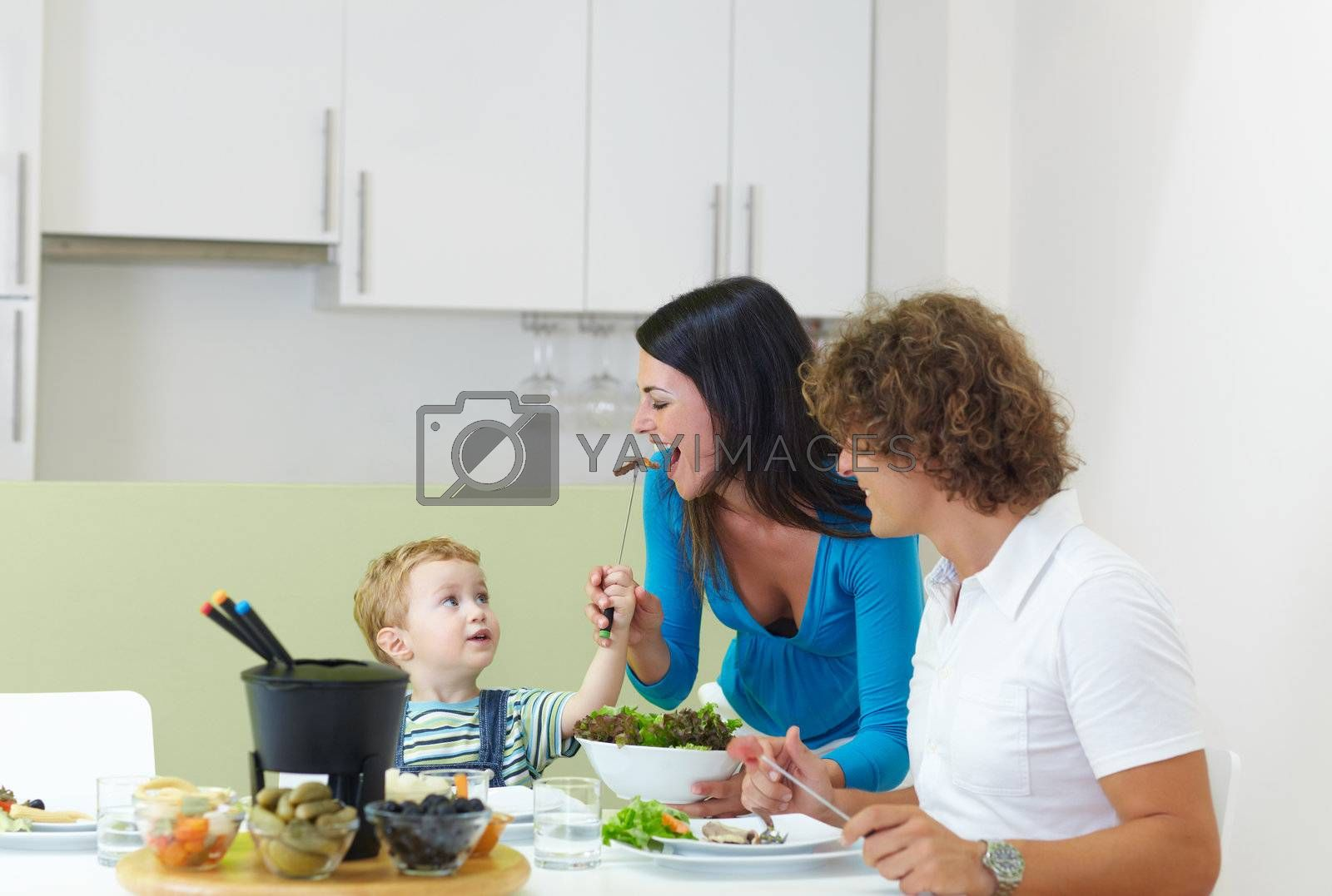 happy family eating meat fondue at home. Copy space