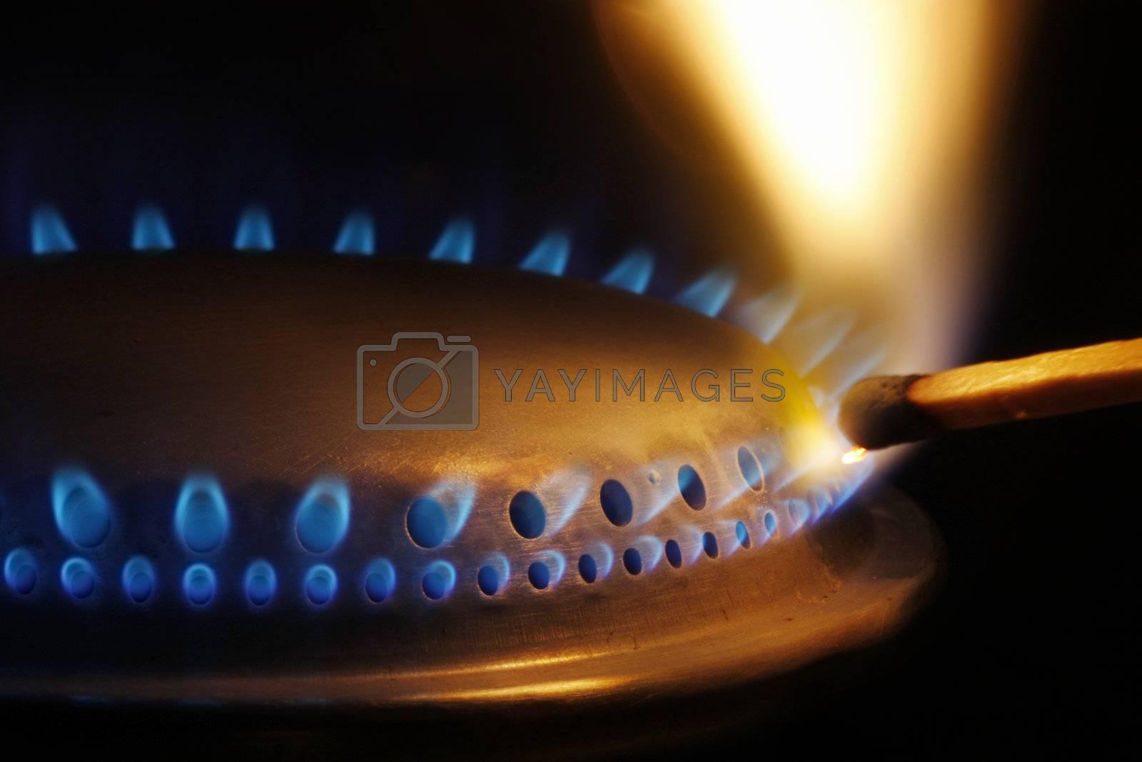 Close-up of a match lightening a gas burner