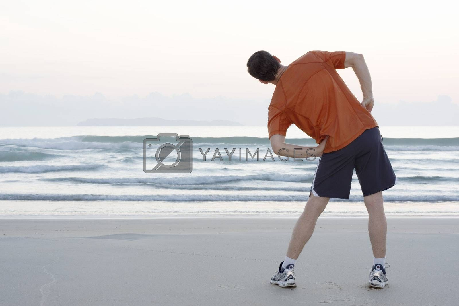 Royalty free image of Jogger doing stretching on a beach by ArtmannWitte