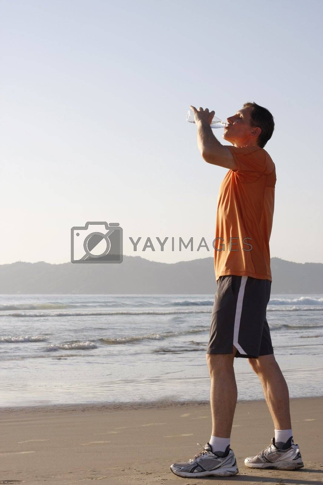 Runner drinking water on a beach
