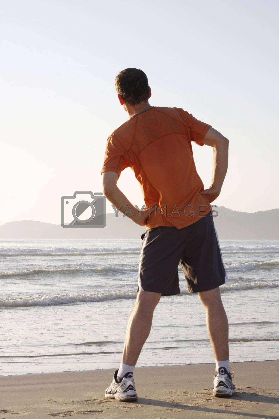 Jogger doing fitness exercises on a beach
