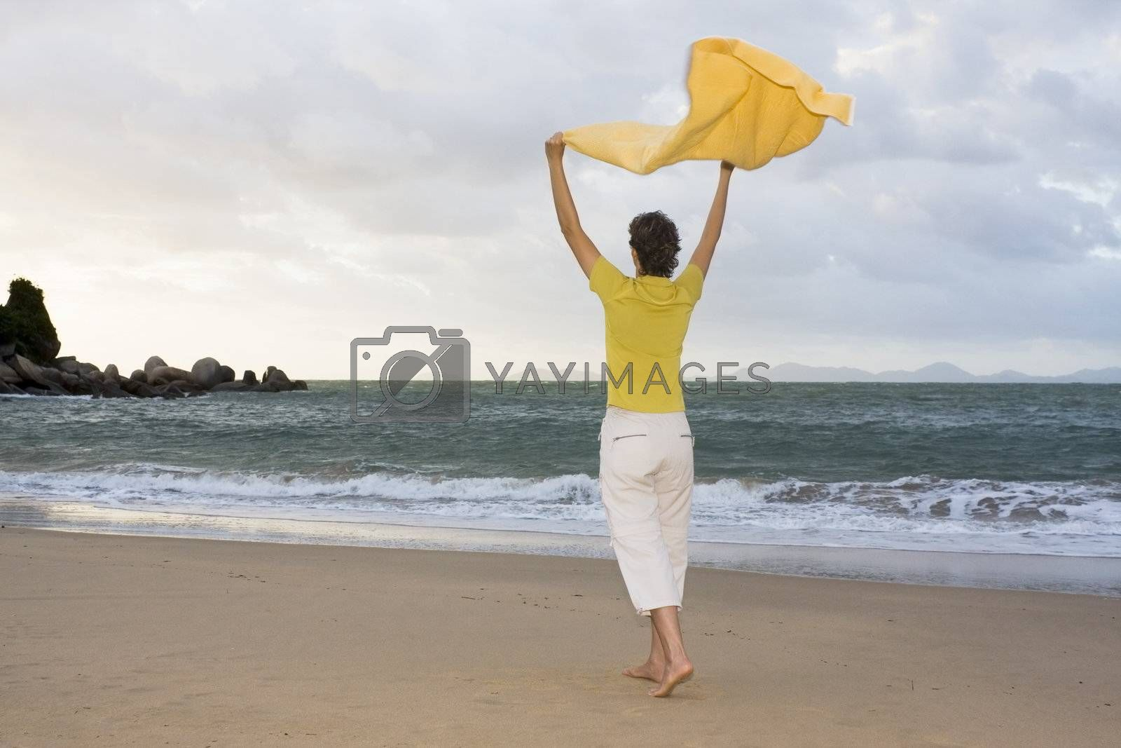 Happy woman walking on a beach with a towel in the wind