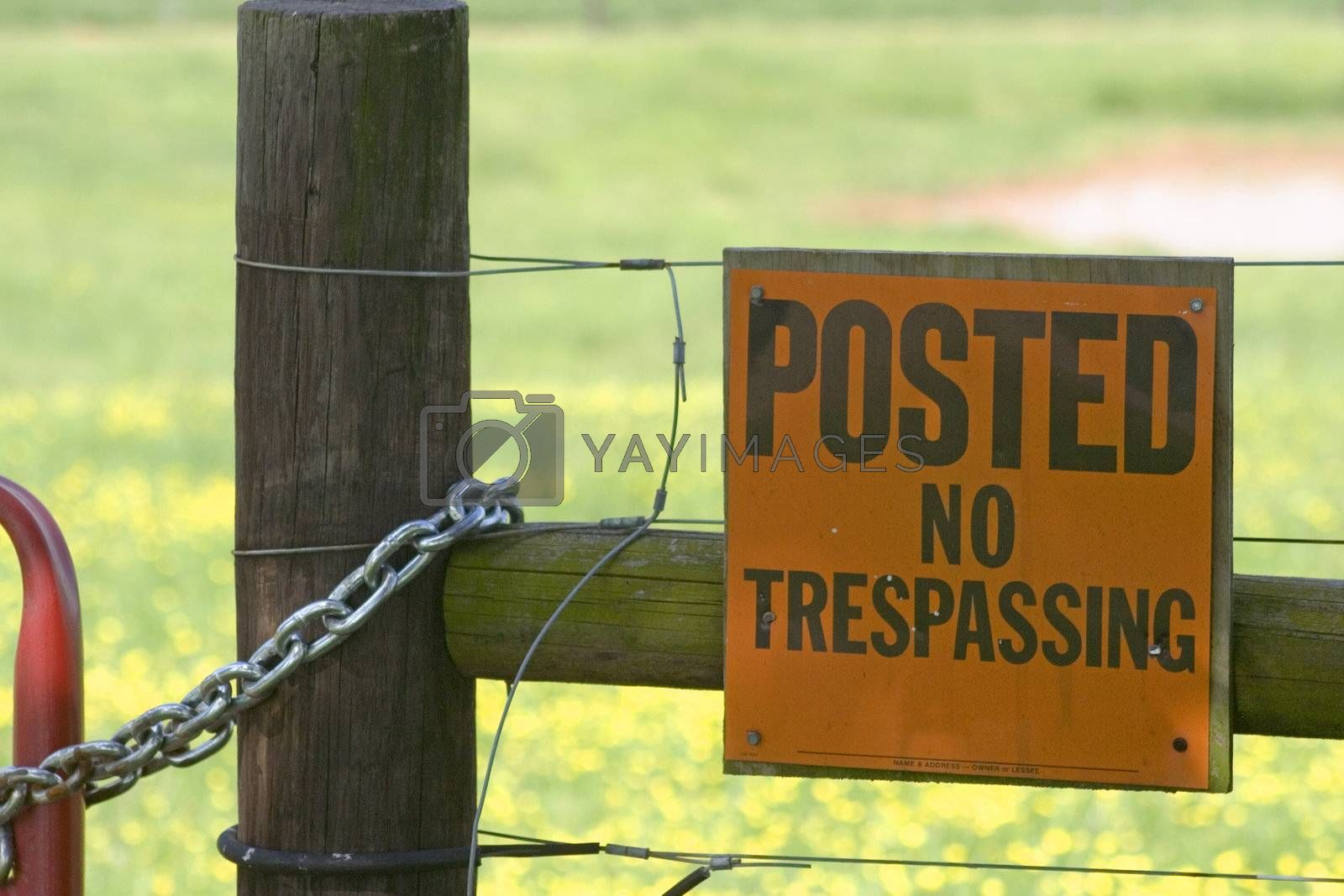 A posted sign that says no trespassing on an electric fence.