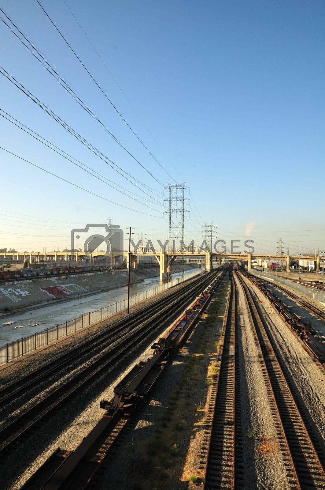 Railroad tracks and power lines converge next to the Los Angeles River in the early morning.  An arching bridge cuts between the industrial smog and the urban graffiti.