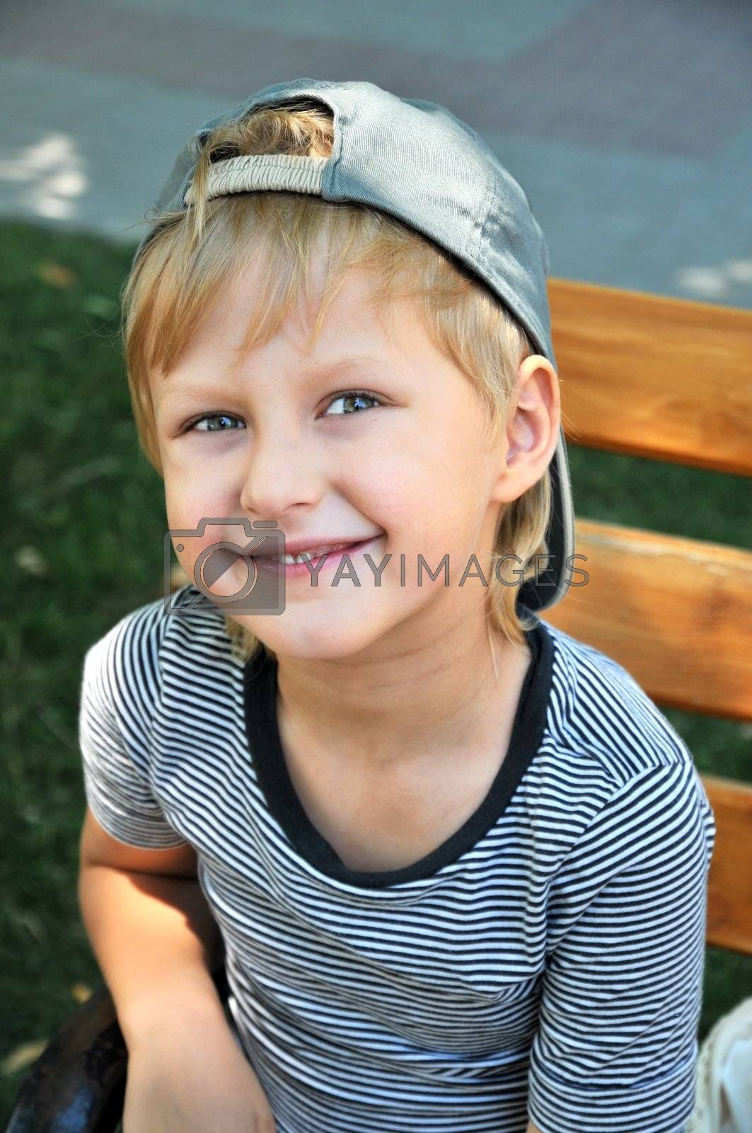 Happy young boy sitting on the bench