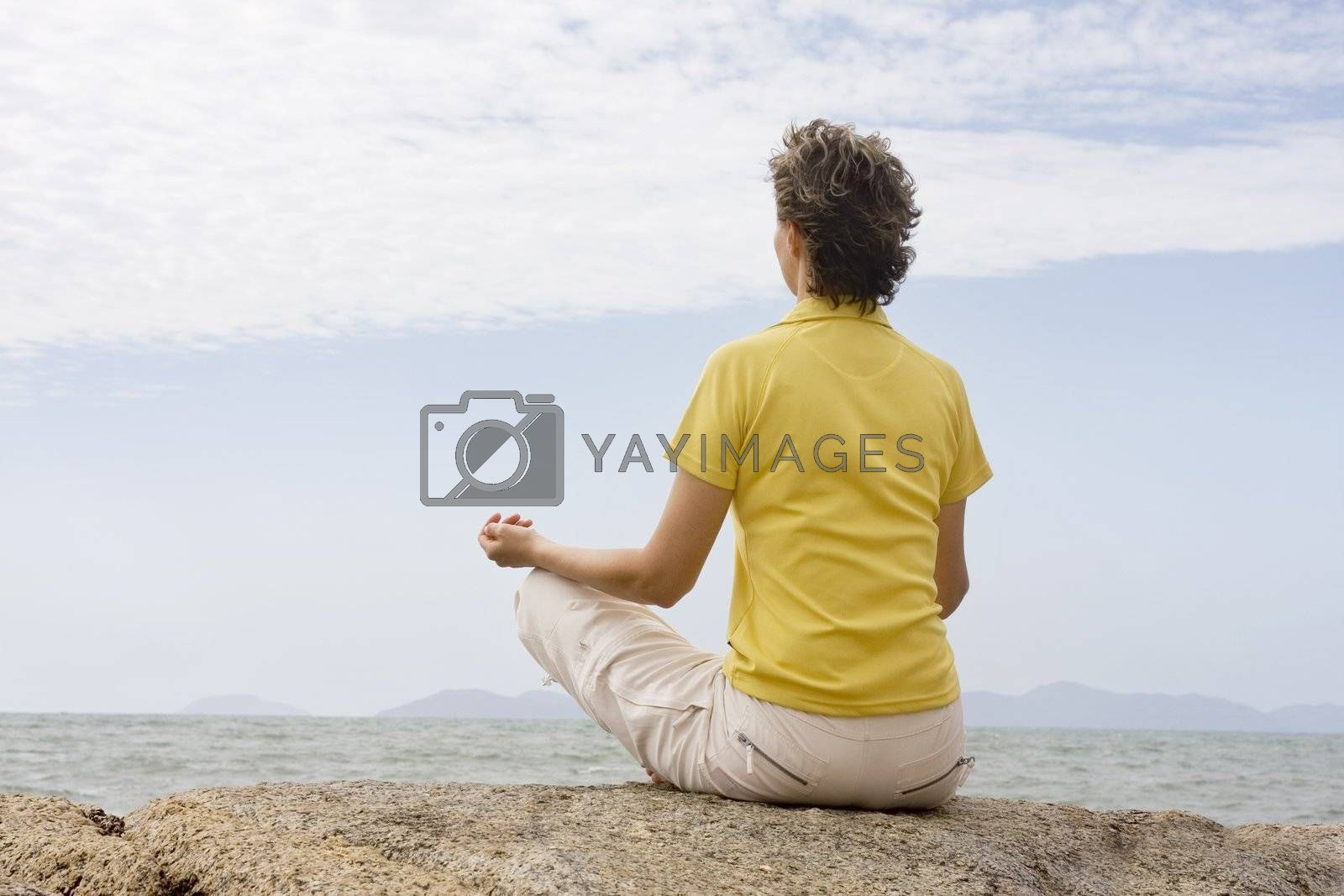 Woman meditating on a rock at the sea
