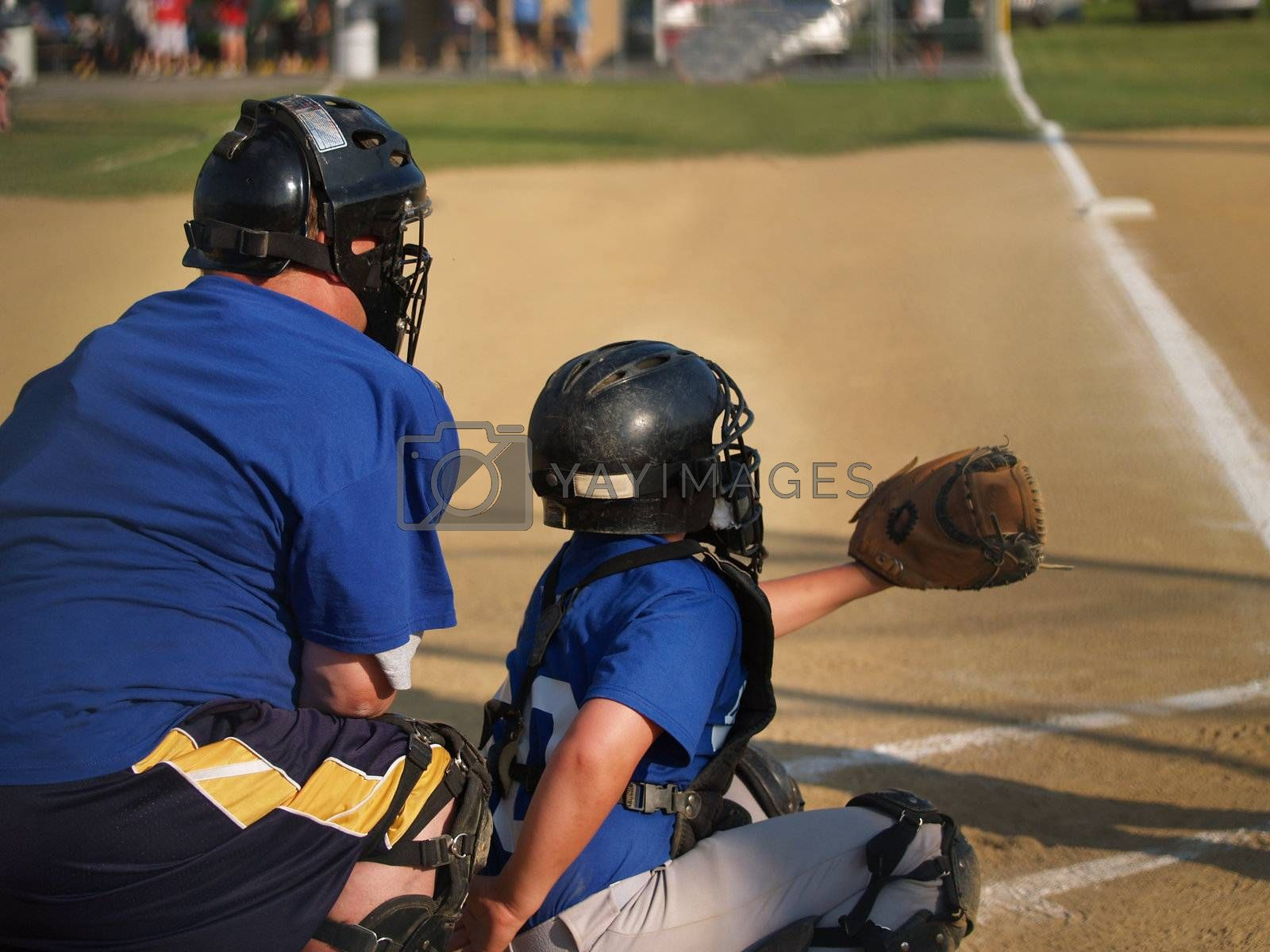 little league baseball catcher and umpire behind home plate