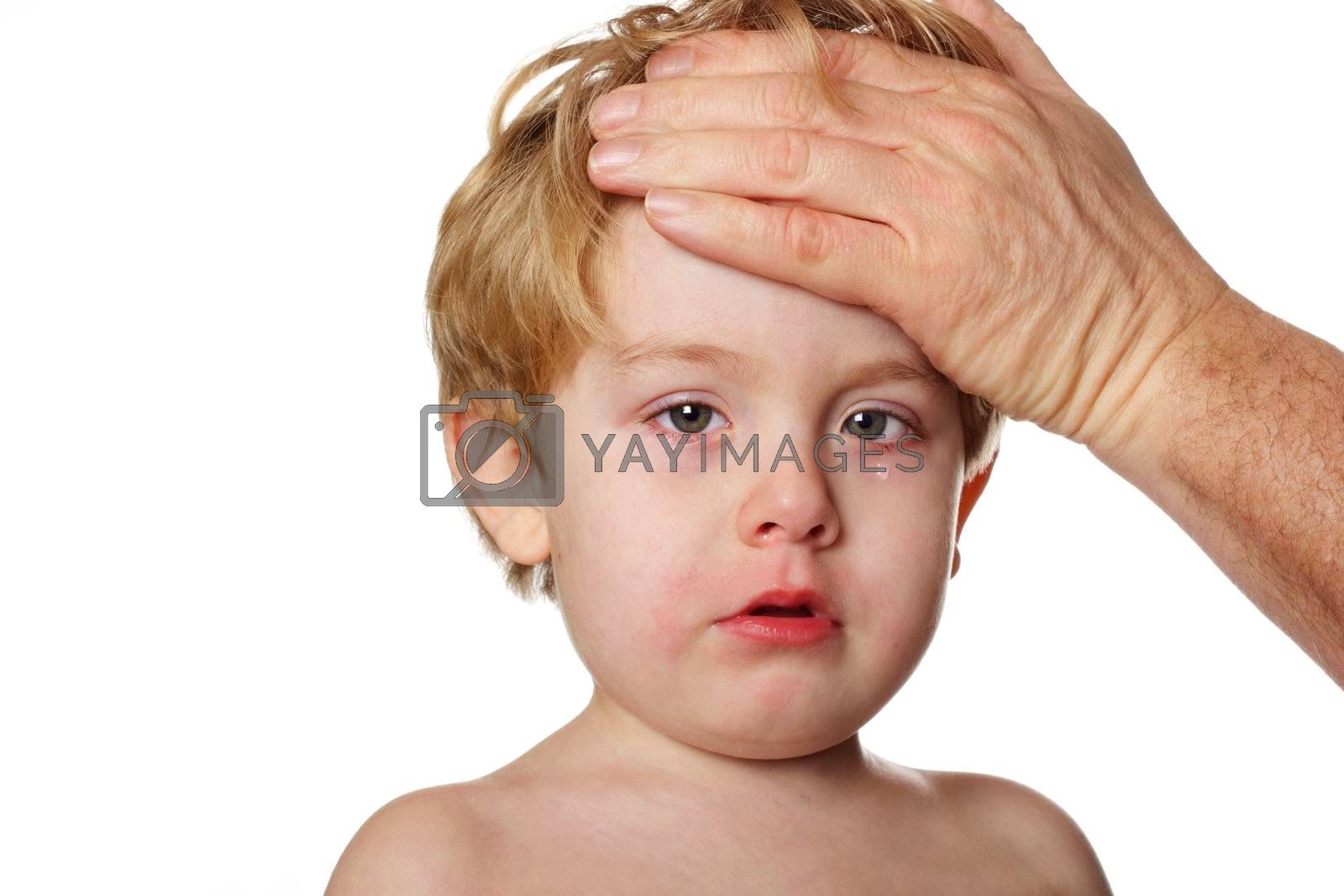 A child with teary eyes looks sad while an adult checks his forehead for fever
