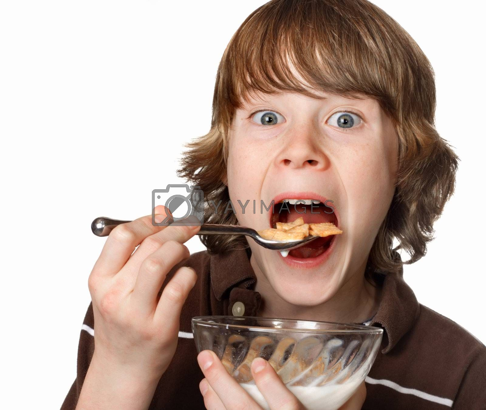A boy opens his mouth wide for a spoonful of cereal