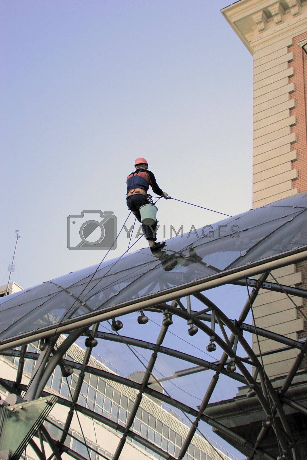 One worker cleaning glass on  building's roof.