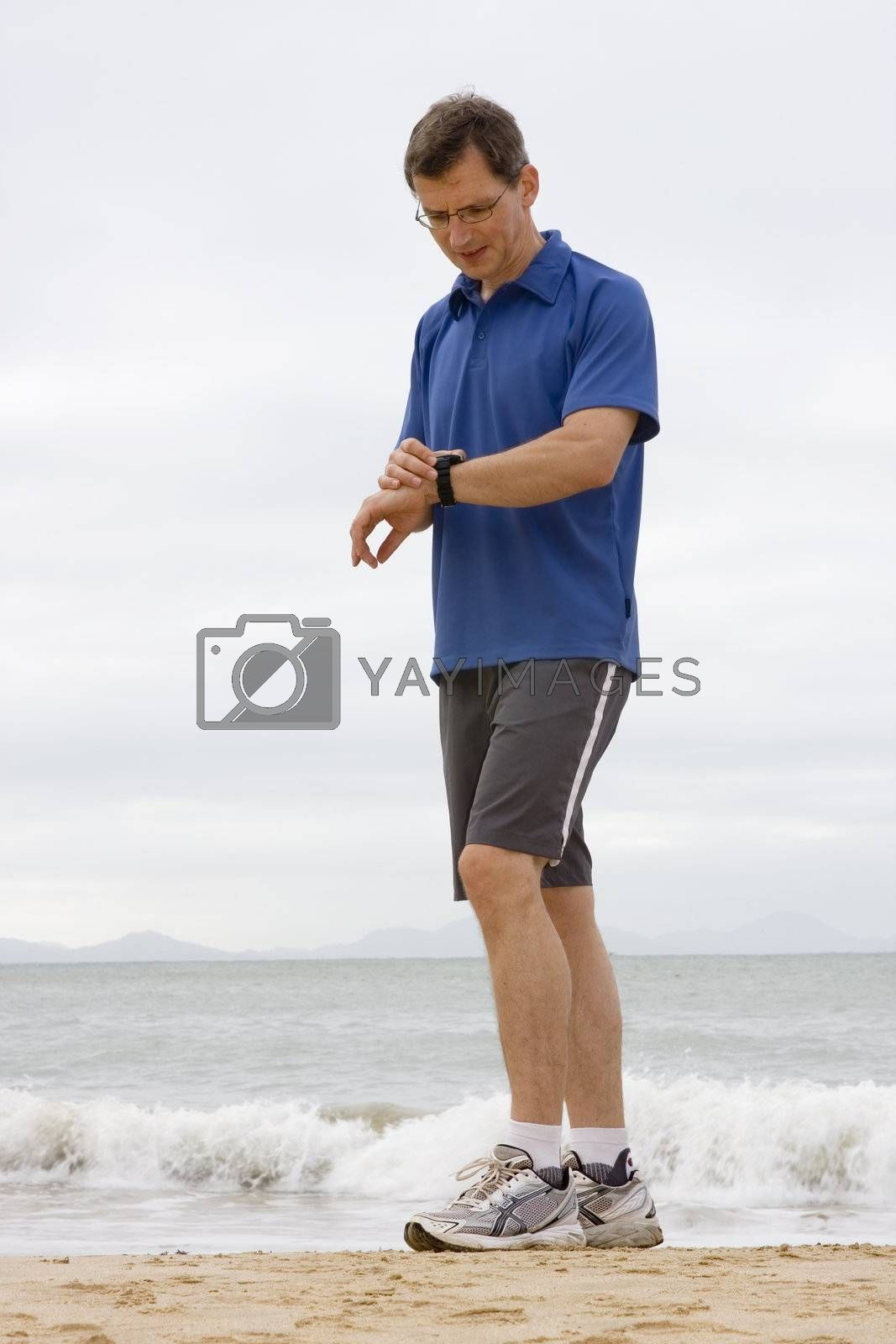 Runner looking at stop watch on a beach