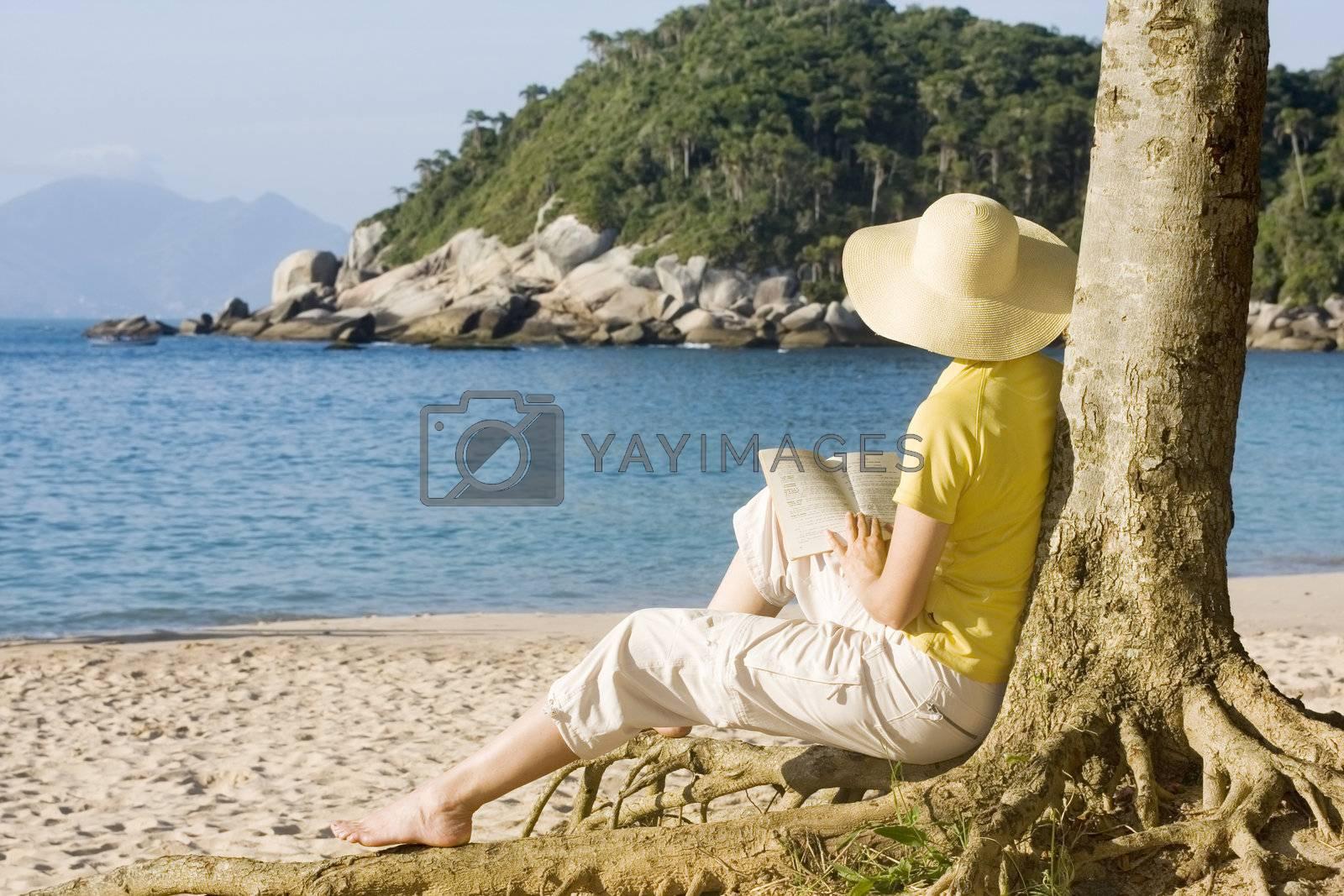 Woman reading a book on a tropical beach - Bombinhas - Brazil