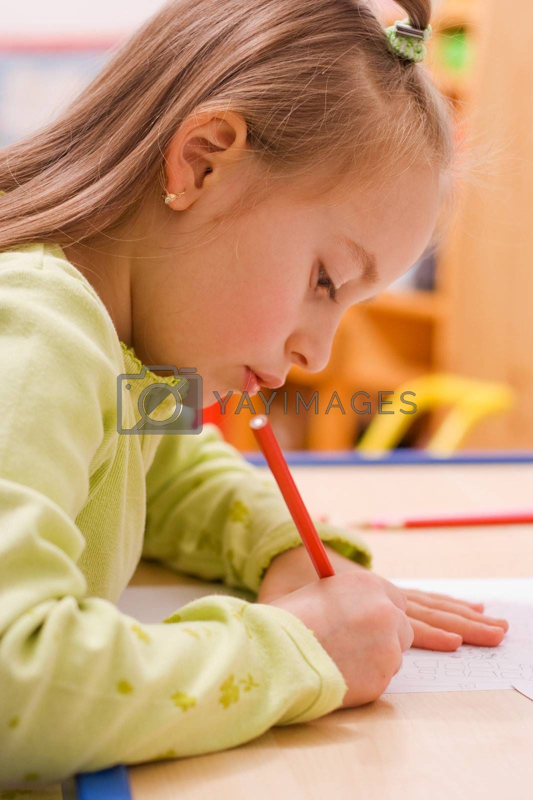 Pretty girl sitting and drawing with red pencil
