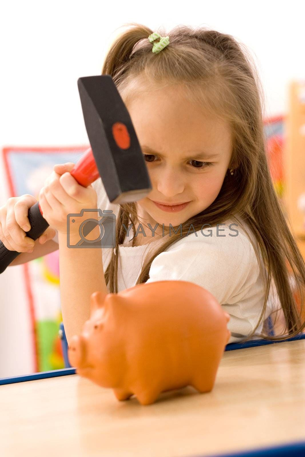 Girl breaking the piggy bank with hammer
