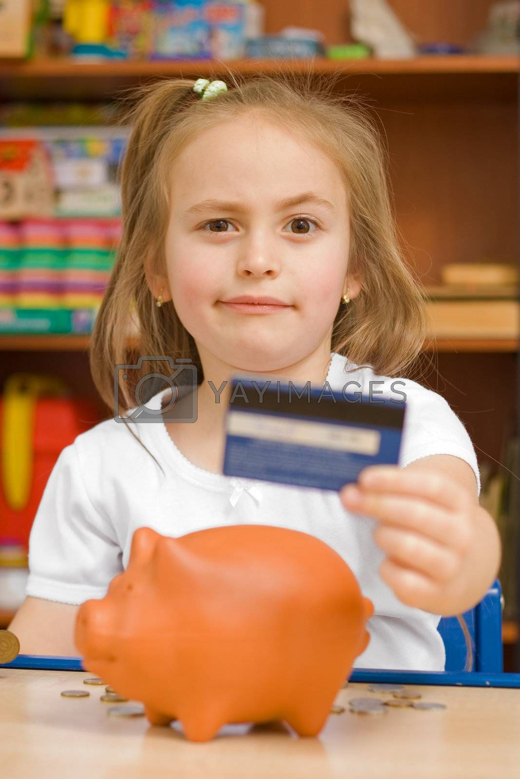 Girl showing credit card against piggy-bank