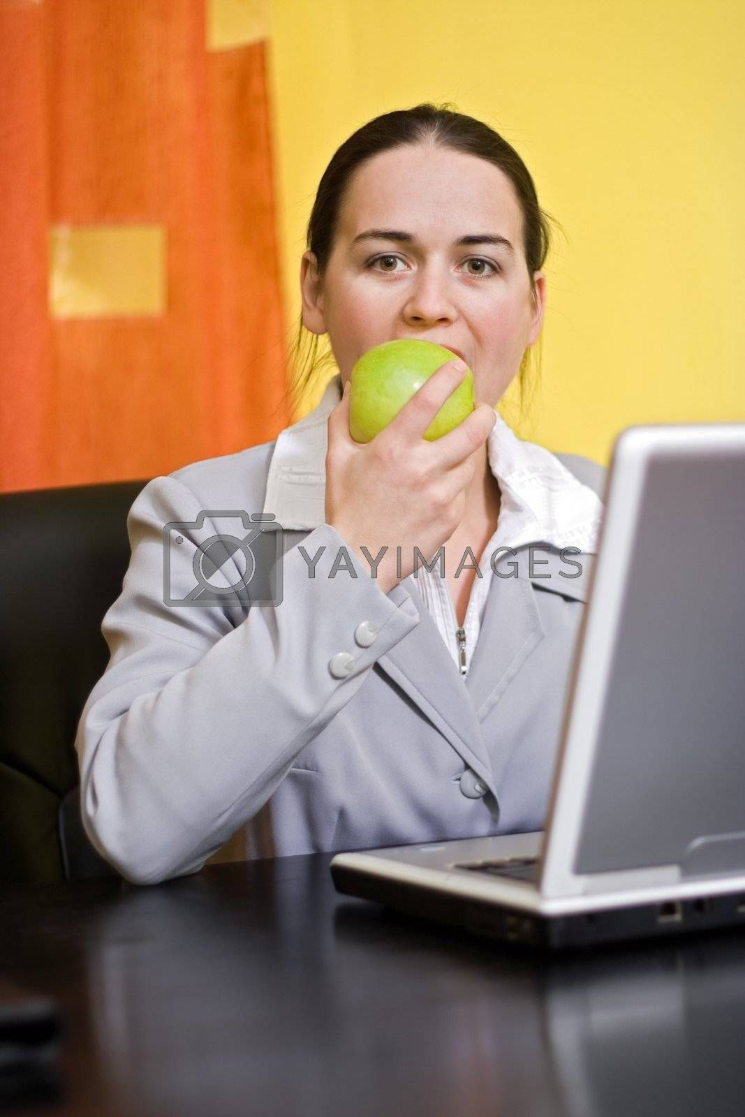 Business woman's healthy bite in a green apple