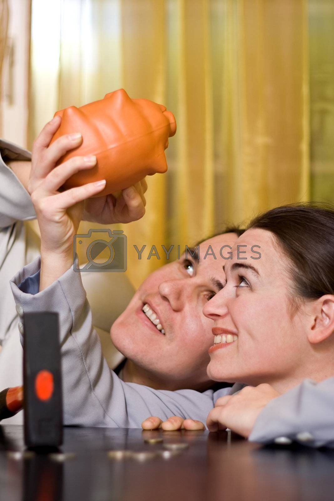 Young couple looking for money in piggy bank - they may break with hammer