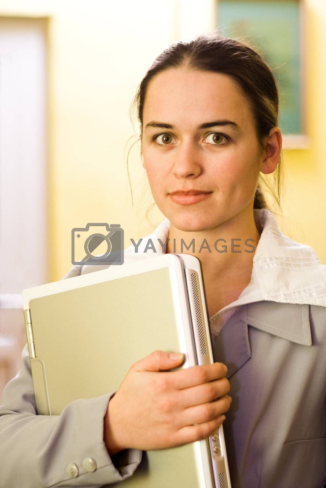 Pretty young woman with silver laptop in hand
