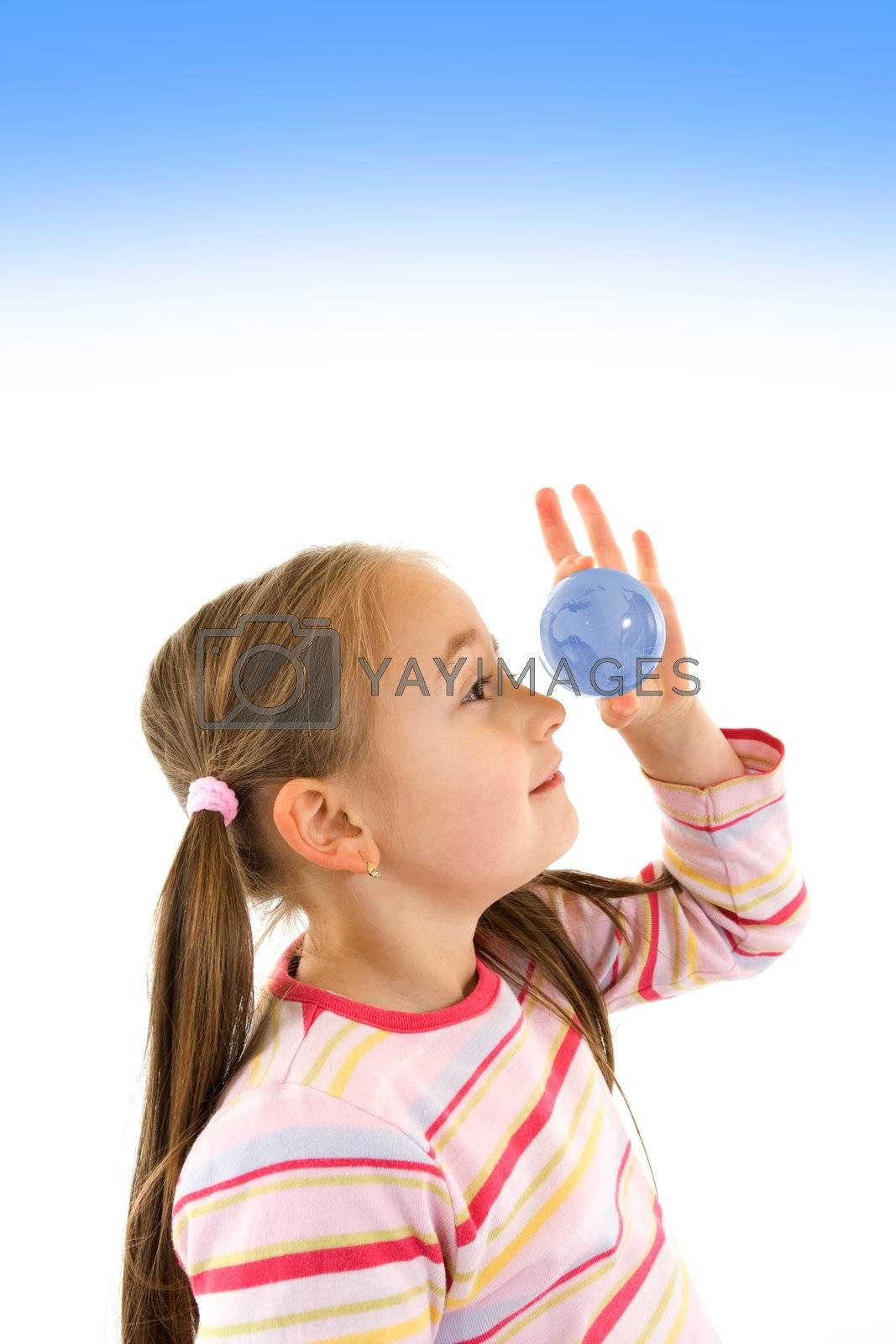 Pretty young girl looking into a glass globe