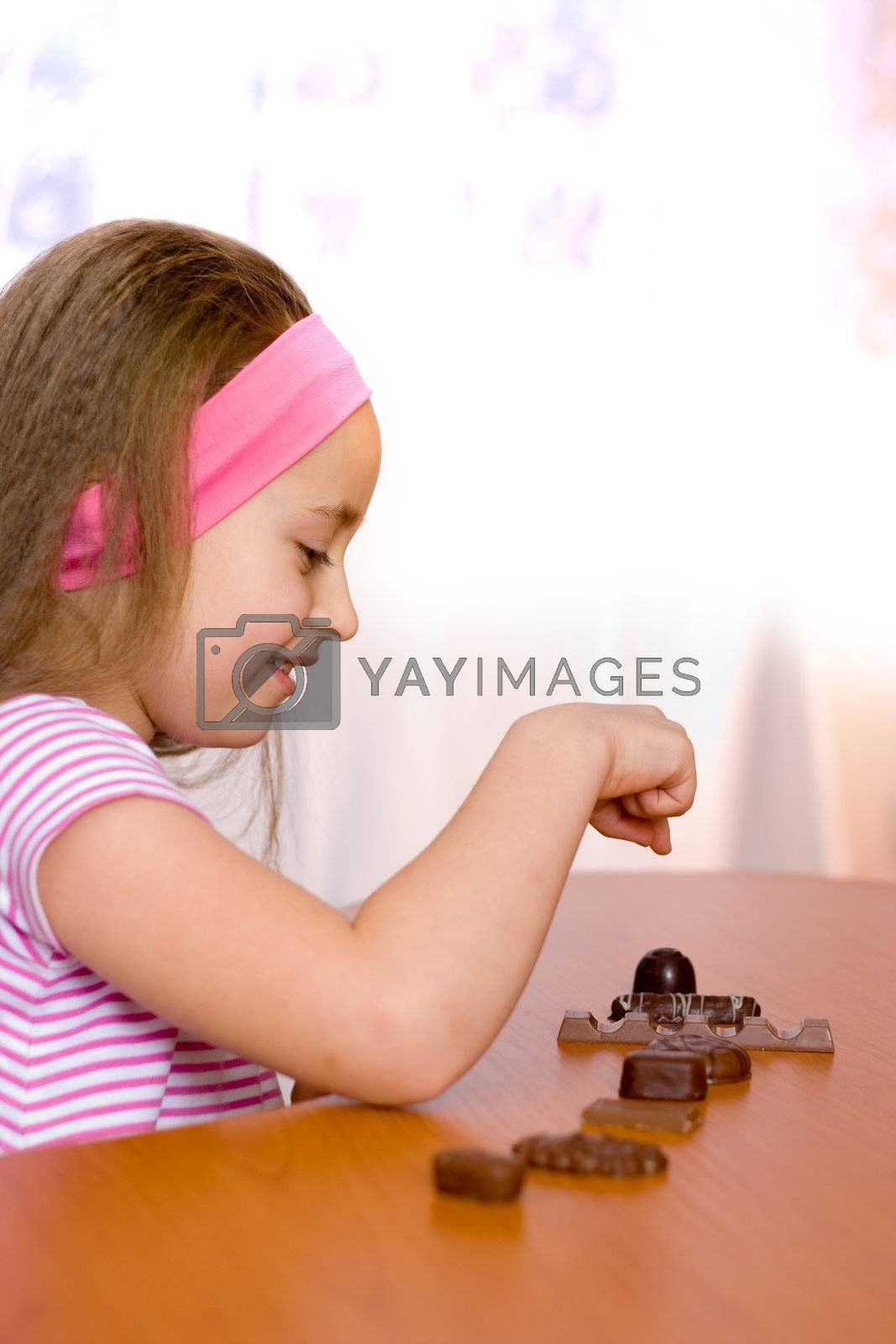 Little girl counting assorted chocolates on table