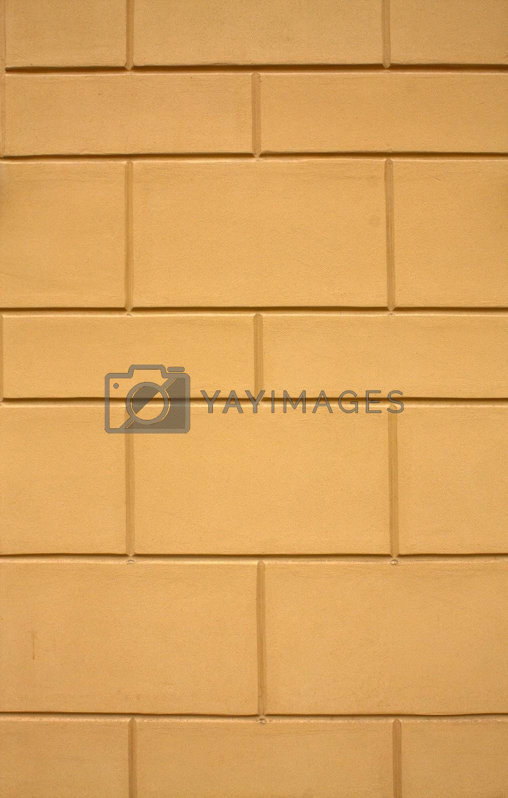 The yellow plastered wall with a regular relief.