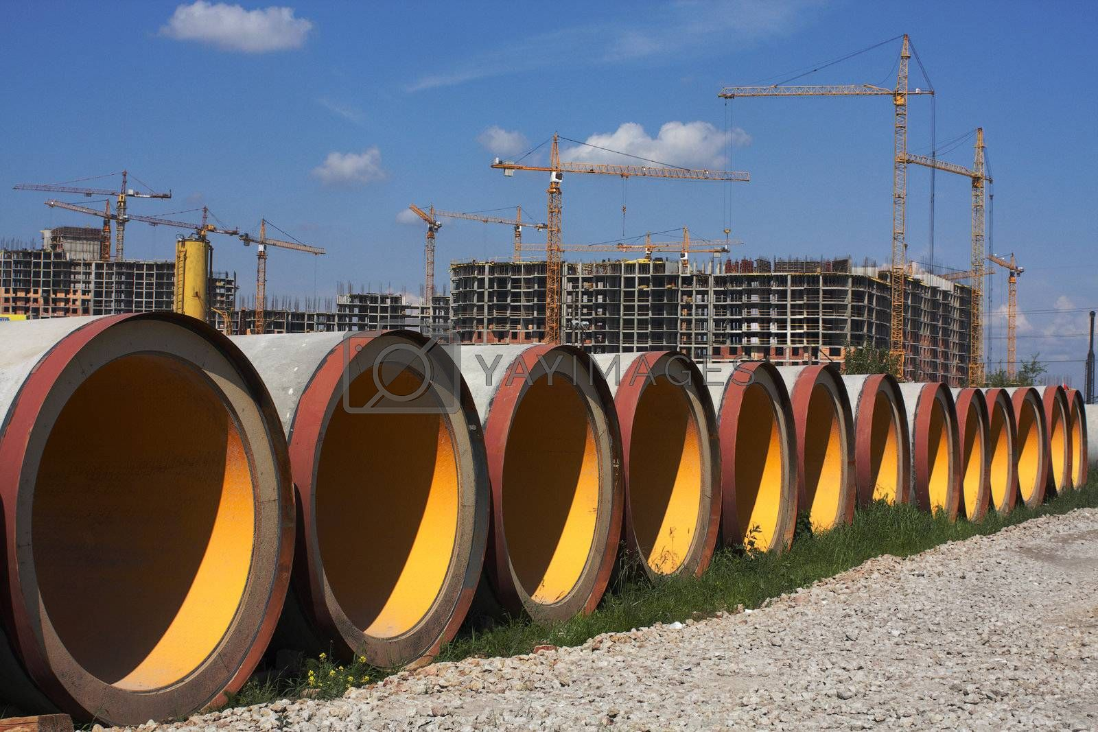 Concrete pipes for construction of new sewer system. Construction of a complex of buildings