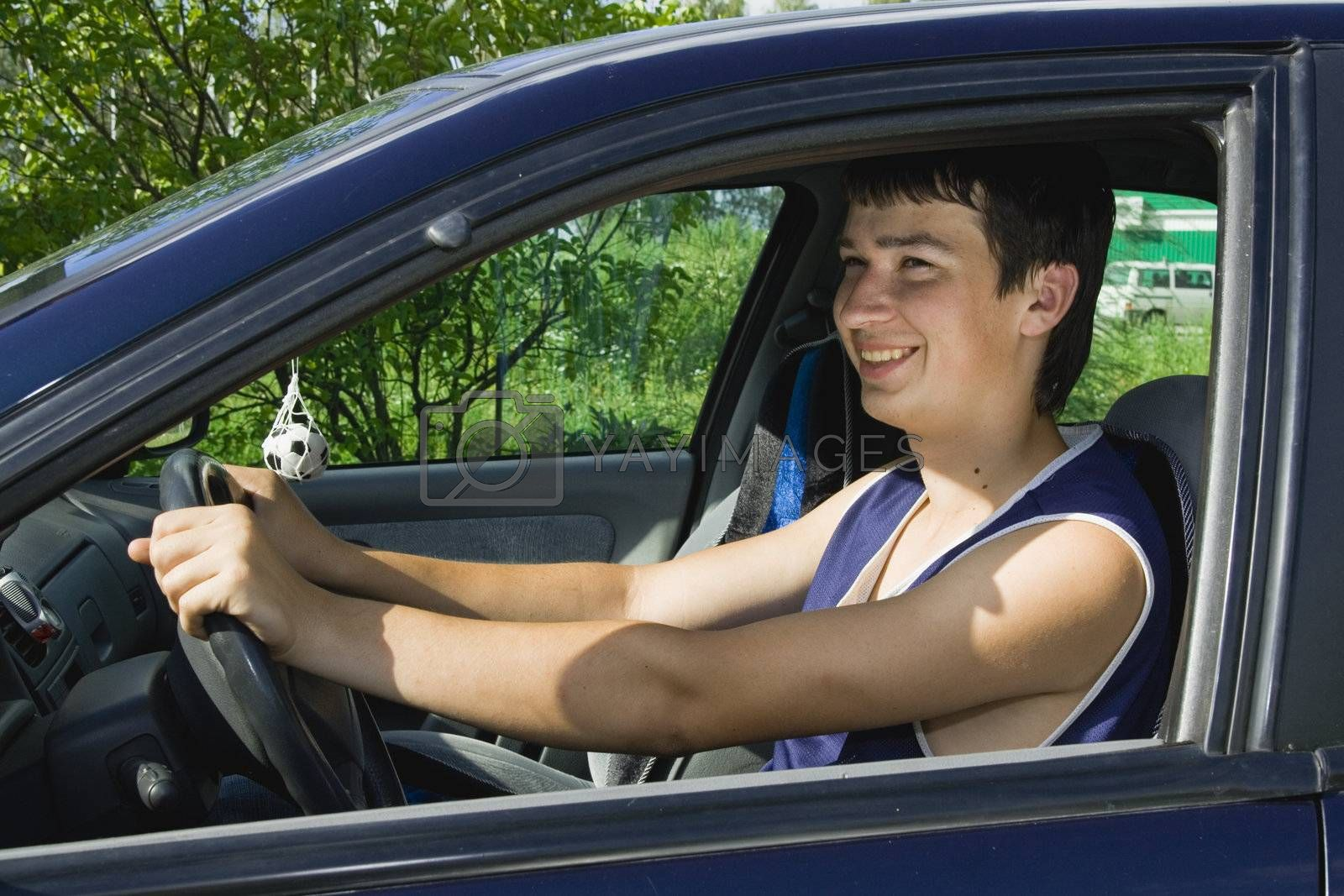 A young man smiling as he sits in a blue car