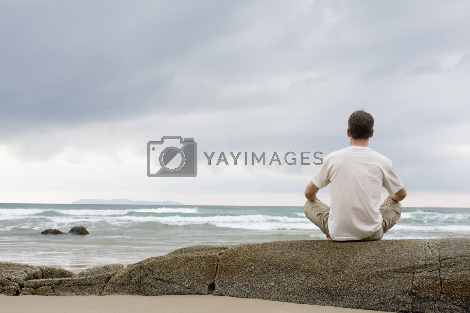 Royalty free image of Man meditating on a rock at the sea by ArtmannWitte