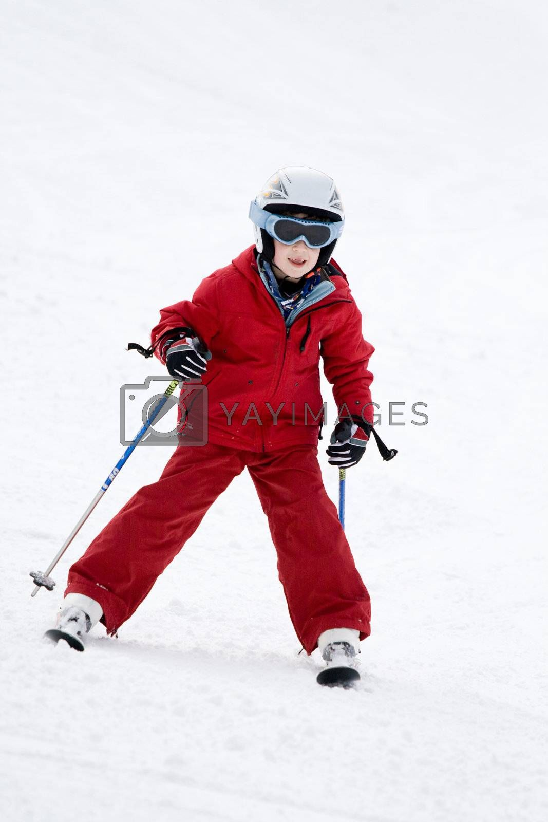Smiling young boy skiing down a snowy slope