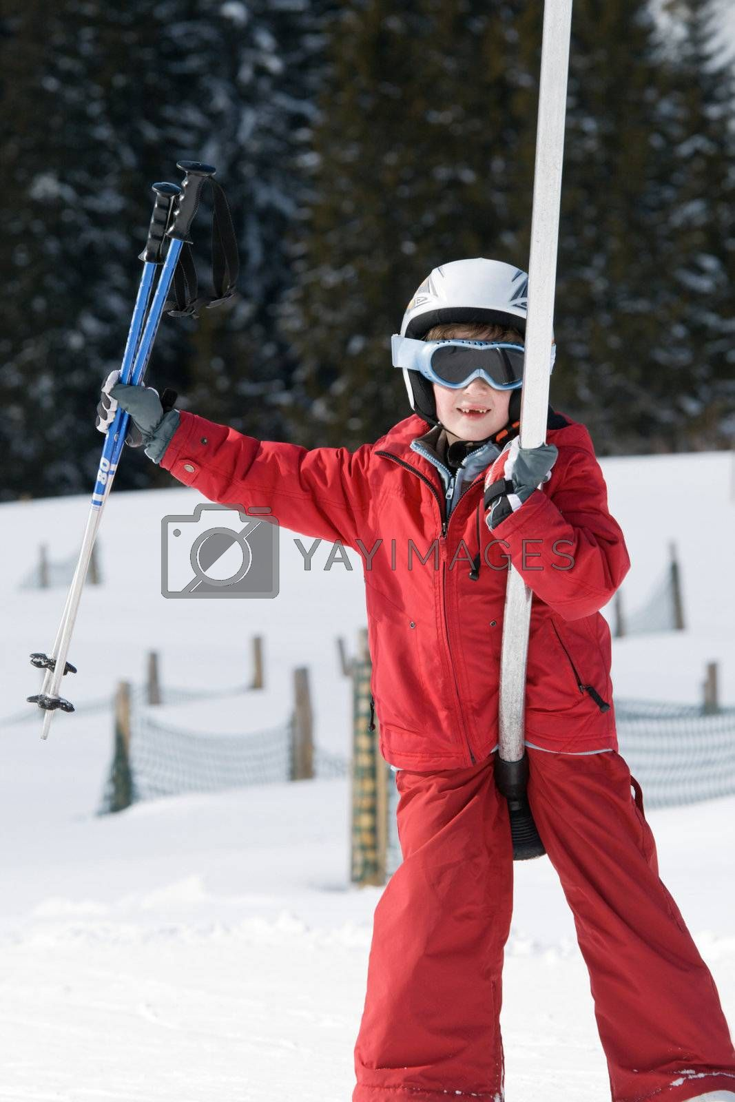 Smiling boy on a ski lift carrying ski poles