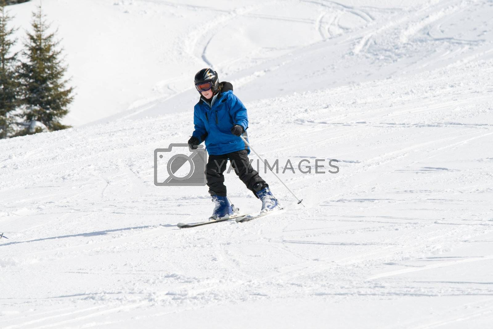 Boy skiing down a snowy slope on a sunny day