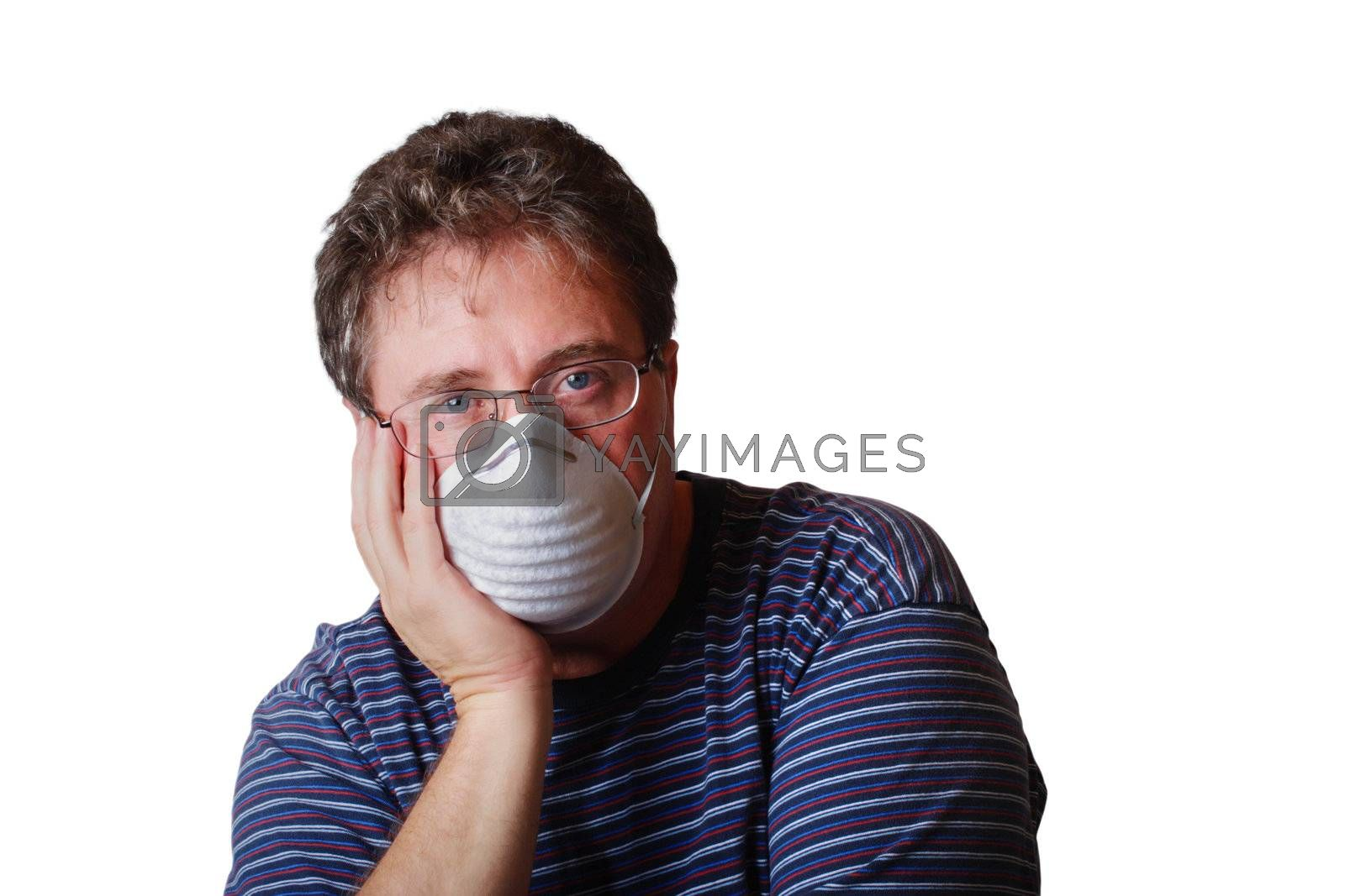 A man with his head resting in his hand is wearing a face mask
