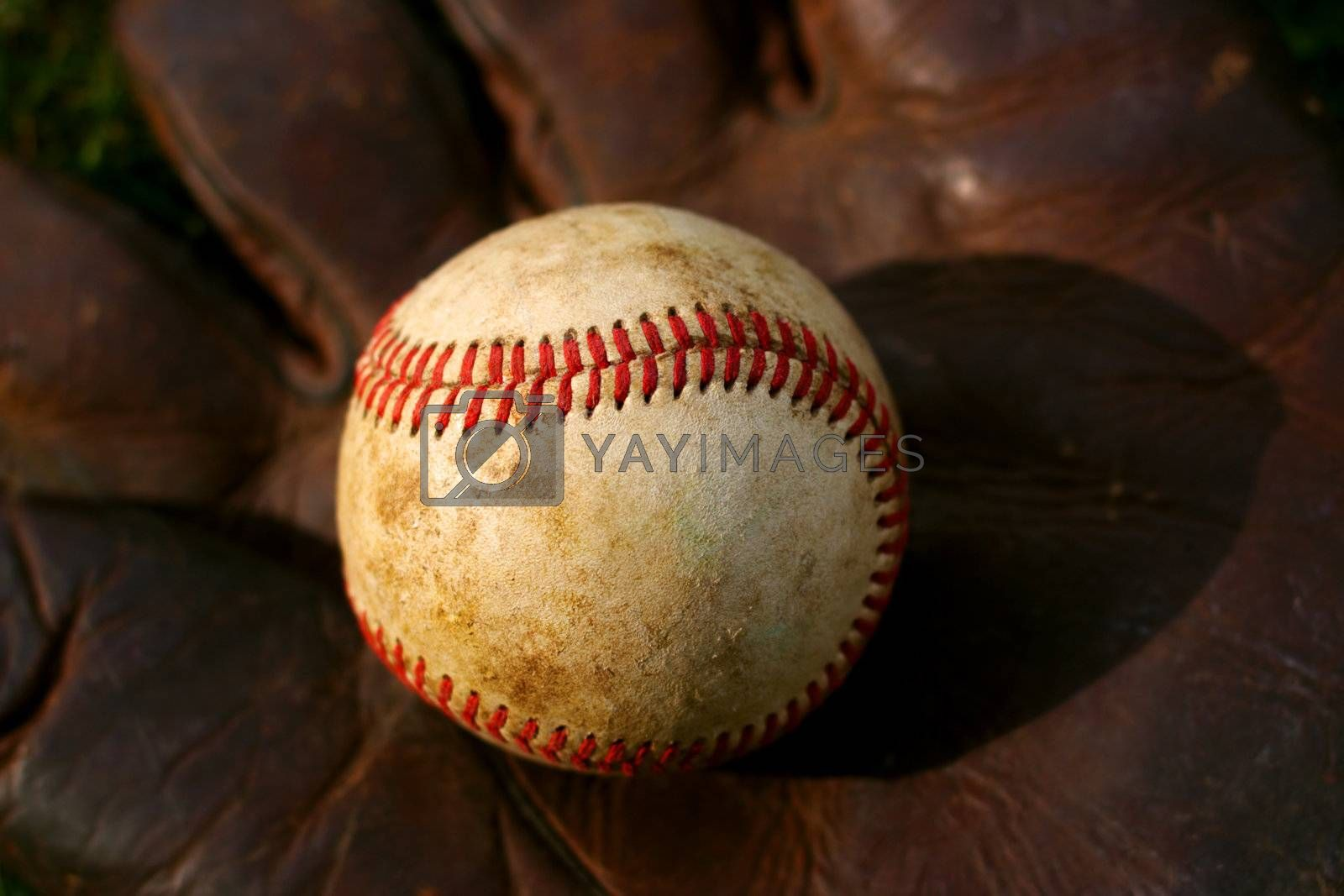 Closeup of an old baseball on a vintage glove