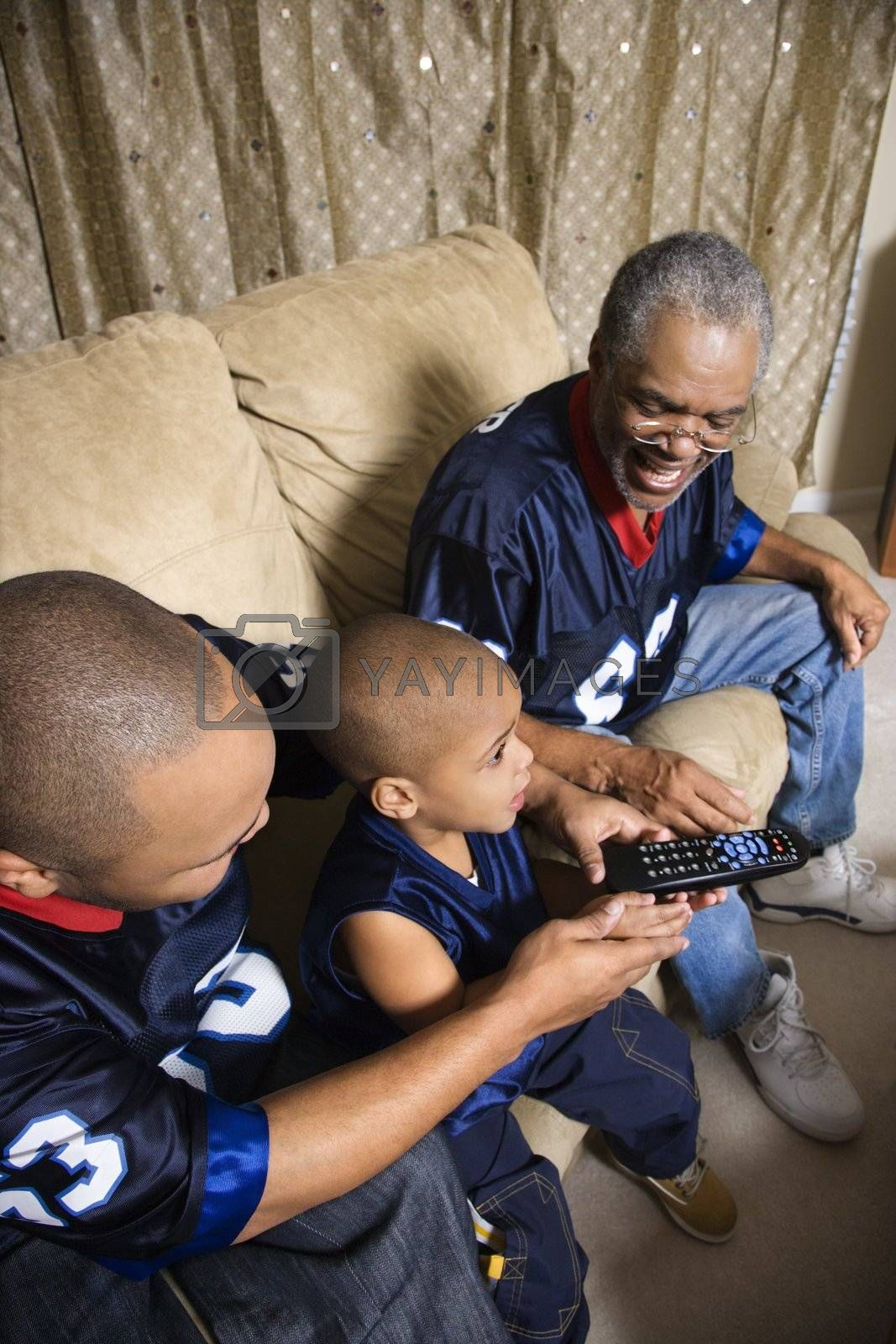Three male generations of an African-American family watching football game on tv with boy holding remote.