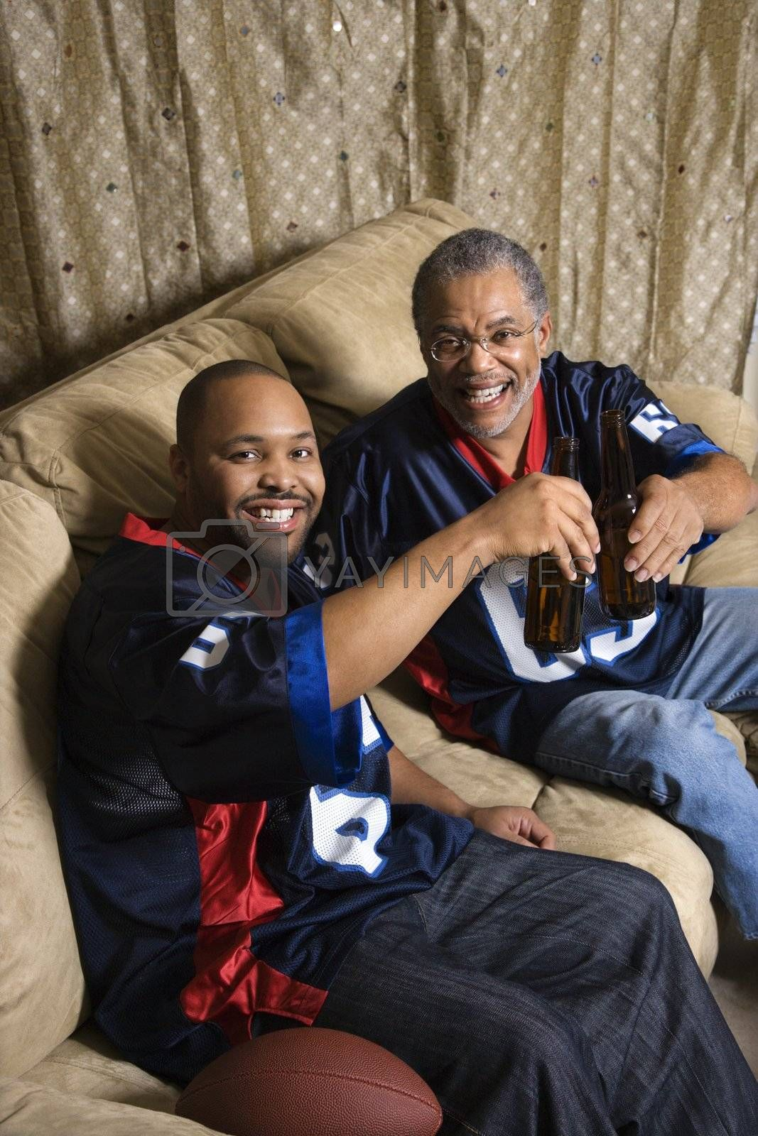 Portrait of an African-American father and son toasting with beer on couch.