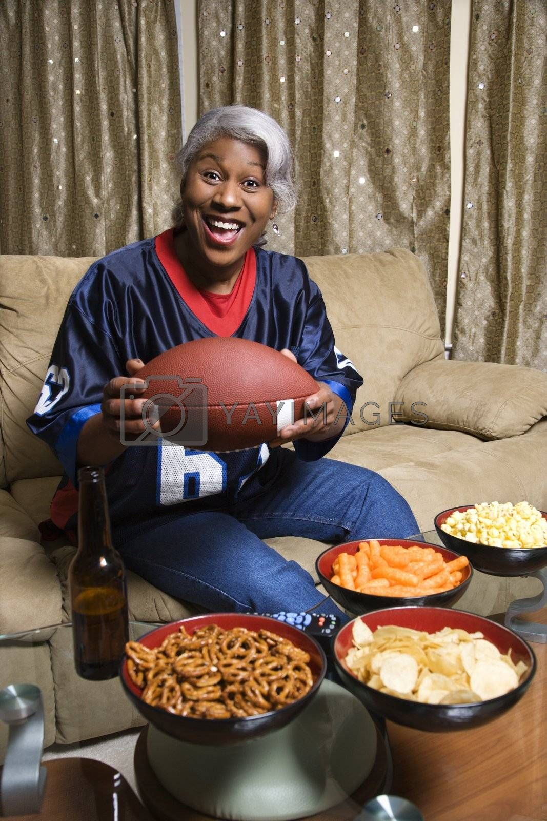 Portrait of smiling Middle-aged African-American woman wearing jersey and holding football.