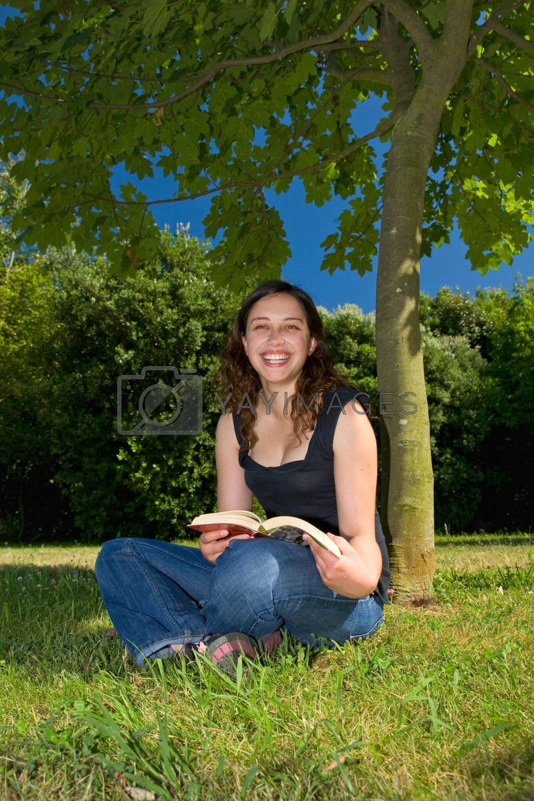 A young girl with a book in a park, smiling.