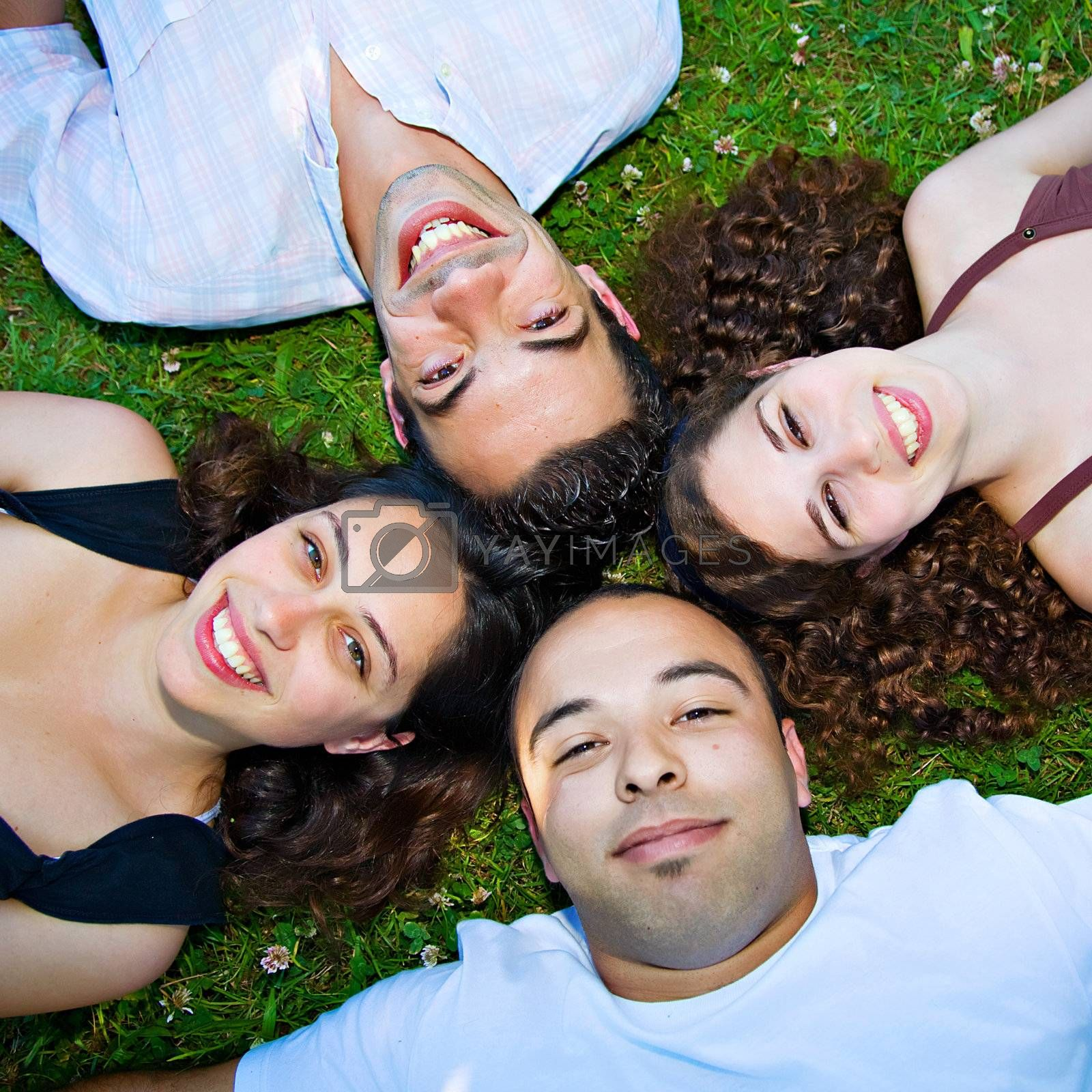Four young people laying down in the grass, smiling.